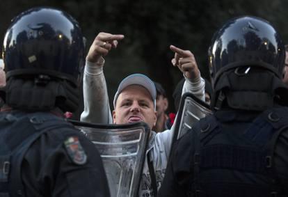 Hooligan che mostra lingua e dita medie davanti due poliziotti