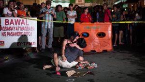 Donna che abbraccia la salma di un caro vittima di esecuzione nelle Filippine