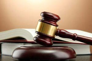 martello del giudice con libro dei codici sullo sfondo